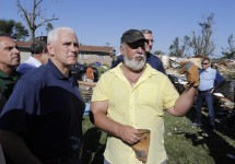 Republican vice presidential candidate, Indiana Gov. Mike Pence talks with Terry Munson, Thursday, Aug. 25, 2016, in Kokomo, Ind. Munson's home was hit by a tornado that passed through the area Wednesday afternoon. (AP Photo/Darron Cummings)