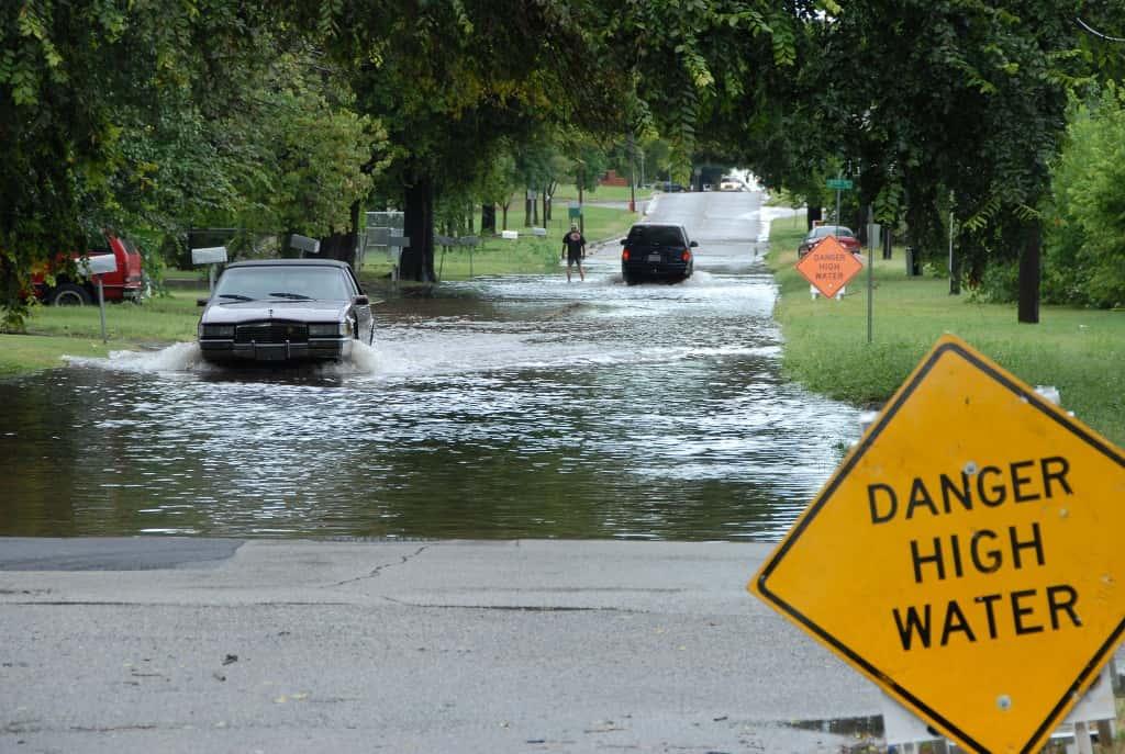 Oklahoma, OK 8-19-07 Cars drive though a flooded street carefully after heading the High Water Danger Signs.  FEMA has a preparedness program to make people aware of the dangers of driving though flooded roads.   Marvin Nauman/FEMA photo
