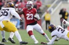 Wisconsin running back Dare Ogunbowale (23) scrambles between Minnesota linebacker Nick Rallis (56) and defensive back KiAnte Hardin (3) during the first half of an NCAA college football game Saturday, Nov. 26, 2016, in Madison, Wis. (AP Photo/Andy Manis)