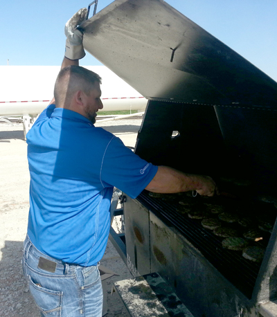 Josh Crouch prepares the Pork Burgers at the West Central Gowrie Farmer sack lunch event...during Pork Month AND Cooperative Month!