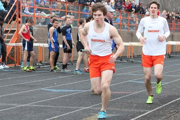Dax Park hands the baton off to Robert Blankenship in the 4 x 800 meter relay in which they took first.
