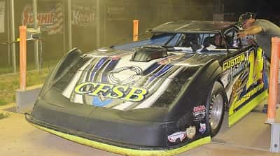 Late Model feature winner Tim Brown rolls across the scales after having the weight of car verified.