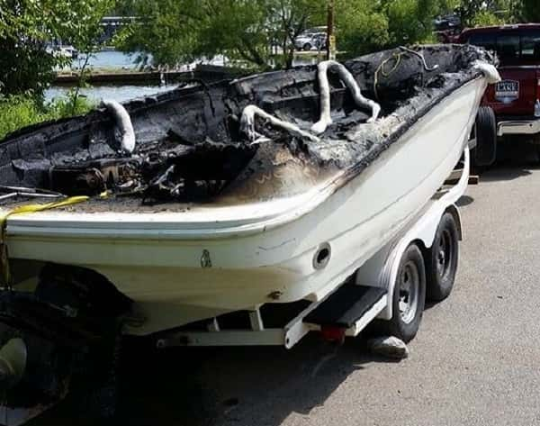 The boat in which a fire injured six people sits on a trailer after removal from the water.