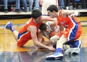 Matthew French (left) and Aaron Reed battle on the floor for the ball with Graves County's Chris Vogt.