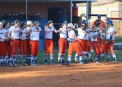 Payton Smothers is greeted by her teammates as she makes her way to home plate following her grand slam.