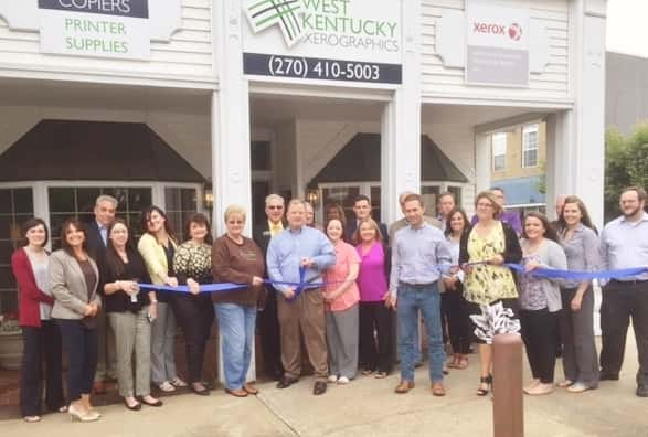 Many friends, family and fellow Chamber members were on hand to help cut the ribbon to kick off the Grand Opening Celebration of West Kentucky Xeroxgraphics on Wednesday May 18th. Jim Dema – Owner and wife Sandra to his left are pictured in the center (w/scissors).