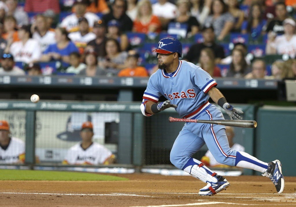 Texas Rangers' Rougned Odor bunts for a single against the Houston Astros in the first inning of a baseball game Saturday, July 18, 2015, in Houston. (AP Photo/Pat Sullivan)