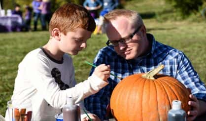 Finnegan Lutz, left, and his dad, Brett Lutz, of St. Joseph, decorate a pumpkin during the inaugural Pumpkin Chunking Challenge held Oct. 10, 2015, at Nimby Pond near Buchanan. The challenge called Launching Hope, and a fundraiser for Safe Shelter for Domestic Violence, featured a pumpkin chunking challenge using a catapult with 300 pounds of weight providing the lift, live music by Terry and The Heartbeats, a pumpkin decorating contest and other activities. The event was organized by Tammie and Keith Stelter, who are members of Safe Shelter's board of directors. Mark Schutze, owner of Nimby Pond, donated the use of his 100-acre site. // Ron DeKett/HP correspondent