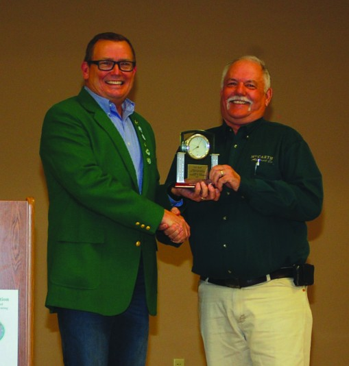 Honored retiree Tim Gray (right) of McCarthy Abstract Co. in O'Neill receives a commemorative clock from Scott Poese. Photo by Terry Miles/The Holt County Independent