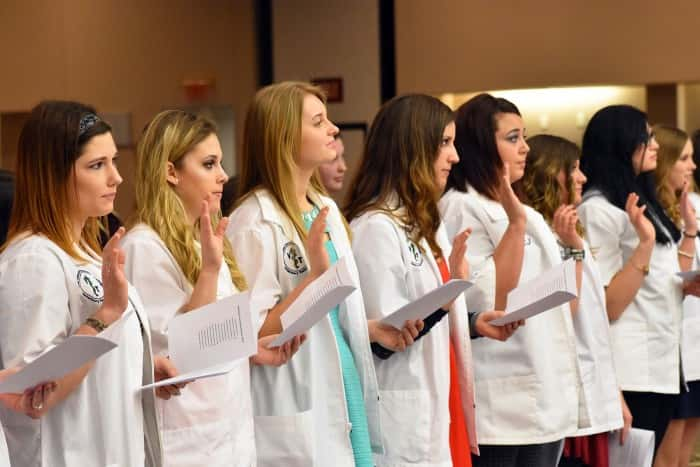 Members of the 2017 and 2018 Veterinary Technology classes at Northeast Community College recite the Veterinary Technician Oath during a White Coat and Pin Ceremony recently in the Lifelong Learning Center. They were among 14 members of the Class of 2018 to receive white coats and 12 sophomores in the Class of 2017 to receive veterinary technician pins. (Courtesy Northeast Community College)