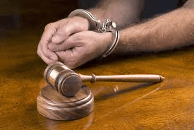 Handcuffed hands gavel