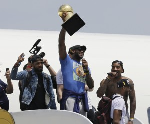 Cleveland Cavaliers' LeBron James holds up the Larry O'Brien Trophy after arriving in Cleveland, Monday, June 20, 2016. James came home with the trophy he promised, and the championship Cleveland has coveted for 52 years. The NBA superstar, born and raised in nearby Akron, stepped off a plane Monday and hoisted the shiny Larry O'Brien Trophy as more than 10,000 fans celebrated the city's first title since 1964. (AP Photo/Tony Dejak)