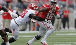 Ohio State quarterback J.T. Barrett, right, scrambles away from Rutgers defensive lineman Kemoko Turay during the first half of an NCAA college football game Saturday, Oct. 1, 2016, in Columbus, Ohio. (AP Photo/Jay LaPrete)