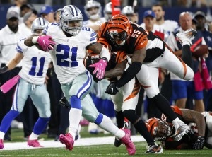 FILE - In this Oct. 9, 2016, file photo, Dallas Cowboys' Ezekiel Elliott (21) evades pressure from Cincinnati Bengals' Dre Kirkpatrick (27) and Vontaze Burfict (55) as Elliott carries the ball during an NFL football game in Arlington, Texas. There remain enough doubters about the Cowboys but the way Dak Prescott is throwing it (155 passes without a pick) and Ezekiel Elliott is running it (league-high 546 yards, Dallas is proving you can win behind rookies. (AP Photo/Ron Jenkins, File)