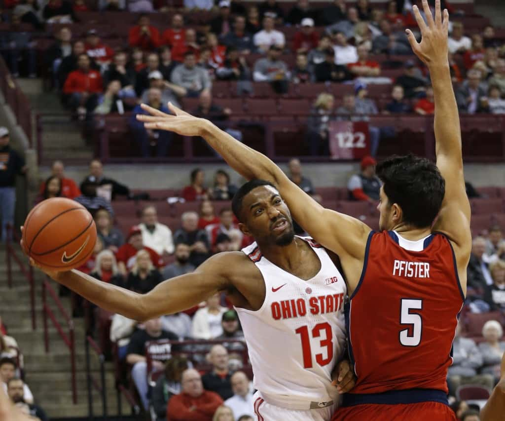 Ohio State's JaQuan Lyle, left, passes the ball around Florida Atlantic's William Pfister during the first half of an NCAA college basketball game Tuesday, Dec. 6, 2016, in Columbus, Ohio. (AP Photo/Jay LaPrete)