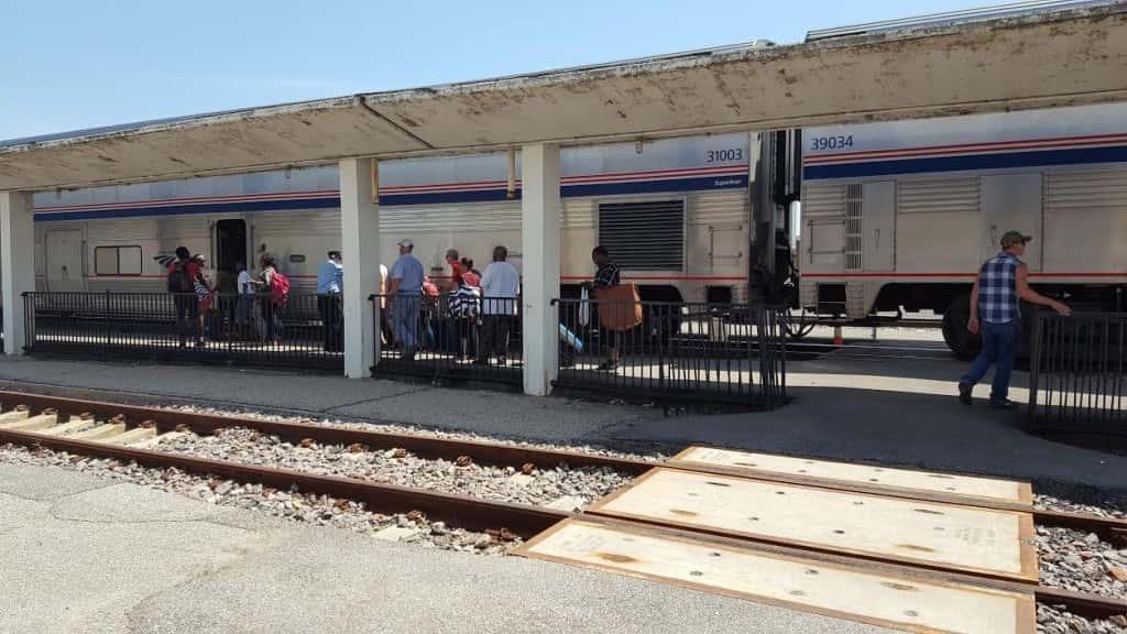 Passengers boarding Amtrak Train at Burlington Depot under a paint-chipped canopy.