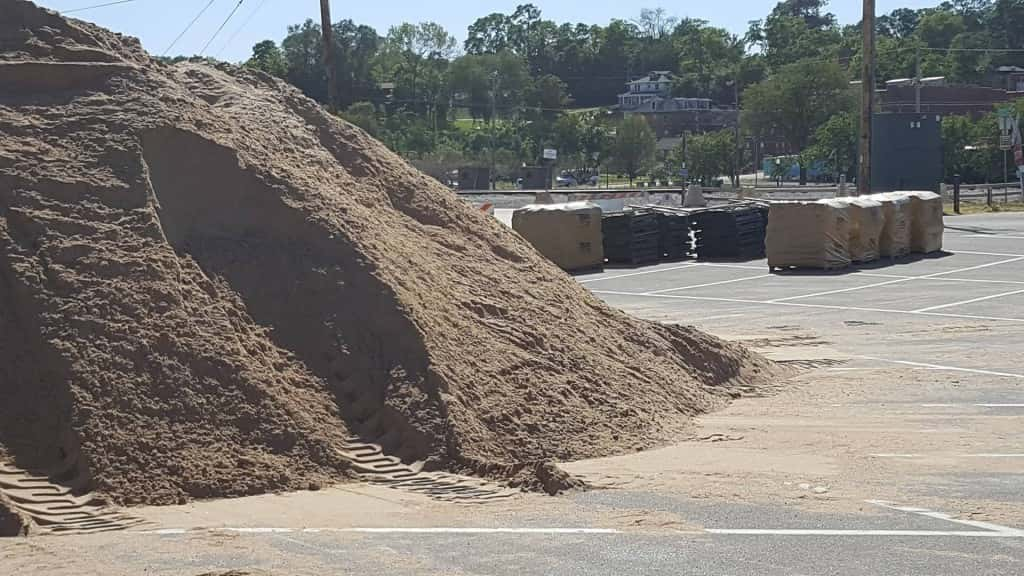 A giant pile of sand sits in the south lot of the Burlington Memorial Auditorium, ready to be poured into the Hesco Barrier casings behind it.
