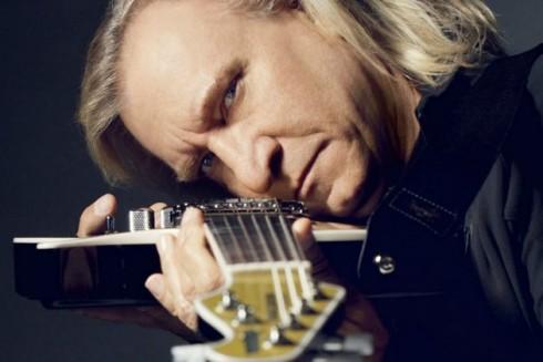 Joe-Walsh-Holding-a-Guitar-and-Sort-of-Squinting-at-the-Camera