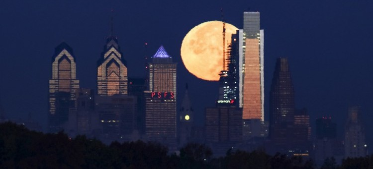 The supermoon sets behind the Philadelphia skyline on Monday, Nov. 14, 2016. The brightest moon in almost 69 years lights up the sky this week in a treat for star watchers around the globe. The phenomenon is known as the supermoon. (AP Photo/Joseph Kaczmarek)