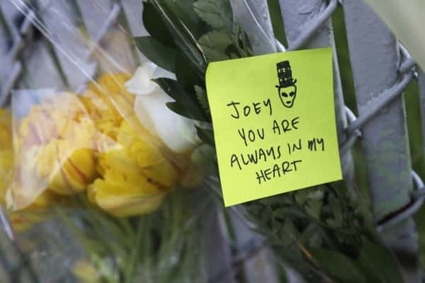 A note with flowers hangs on a fence near the site of a warehouse fire Monday, Dec. 5, 2016, in Oakland, Calif. The death toll in the Oakland warehouse on Friday fire climbed Monday with more bodies still feared buried in the blackened ruins, and families anxiously awaited word of their missing loved ones. (AP Photo/Marcio Jose Sanchez)