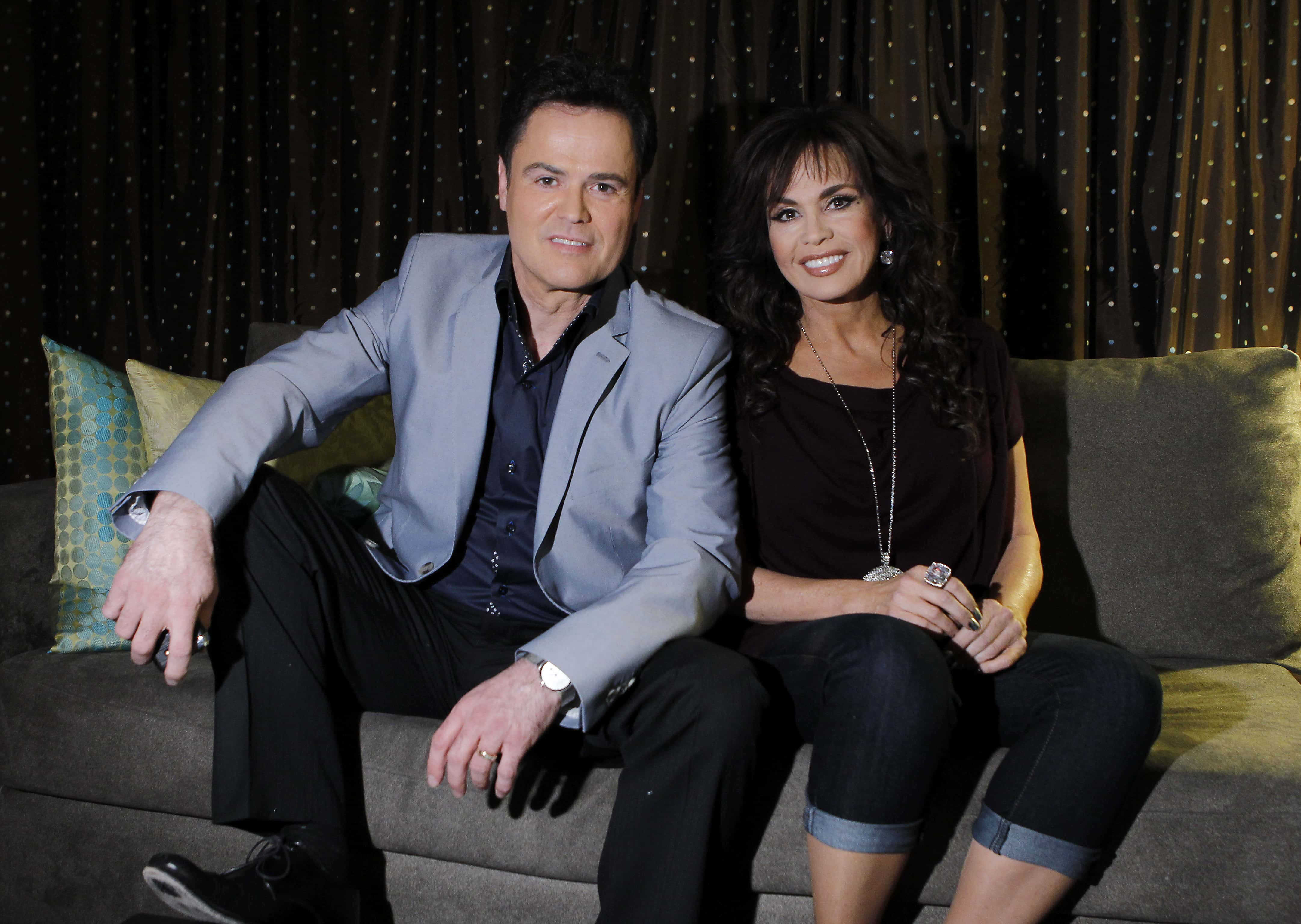 FILE - In this April 28, 2011 file photo, siblings Donny Osmond, left, and Marie Osmond pose backstage at their show at the Flamingo hotel and casino in Las Vegas. Donny and Marie Osmond will be singing at the Flamingo Las Vegas at least through the end of 2015. Caesars Entertainment Corp. announced Monday, Dec. 22, 2014, that the duo has signed on to keep performing at the hotel-casino through the end of next year. (AP Photo/Isaac Brekken, File)