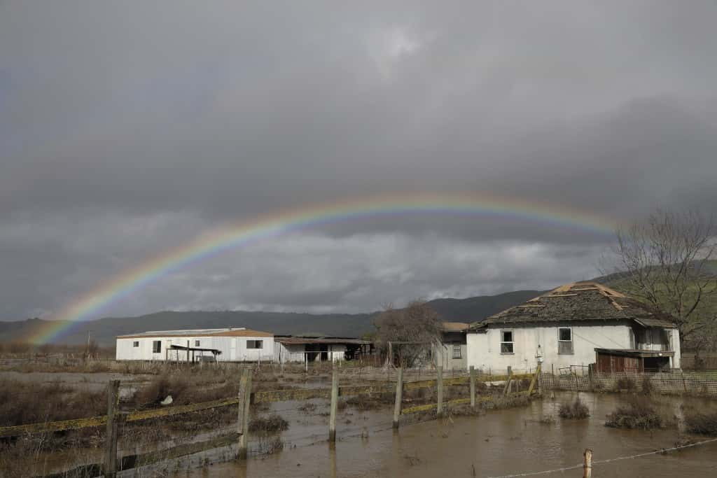 A rainbow is seen over a flooded landscape Wednesday, Jan. 11, 2017, in Hollister, Calif. Forecasters said rain and snow would continue through Thursday, but the brunt of the system had passed after delivering the heaviest rain in a decade to parts Northern California and Nevada. (AP Photo/Marcio Jose Sanchez)