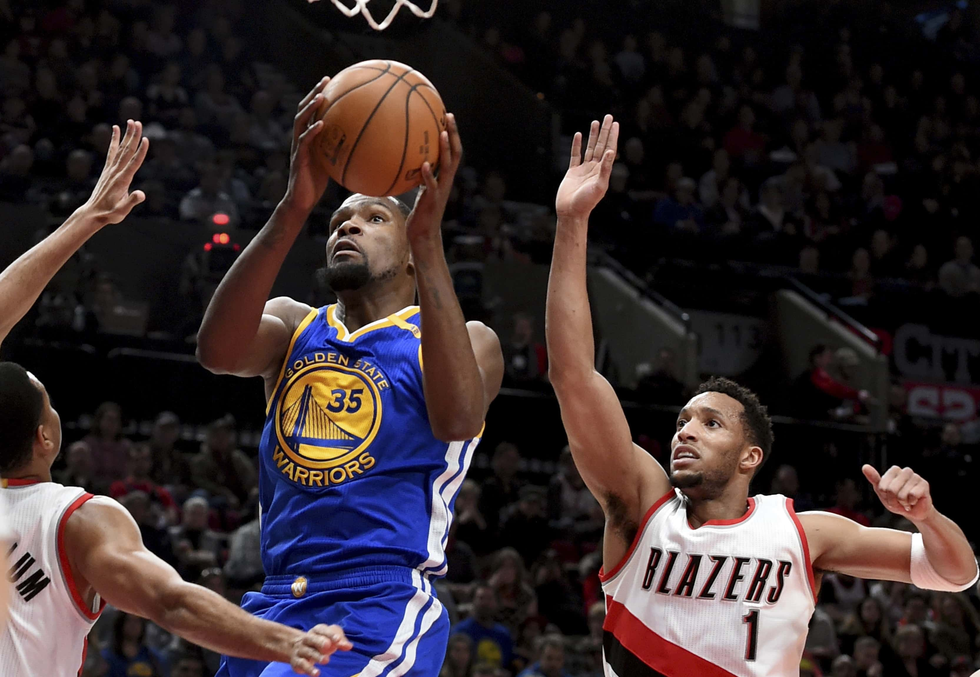 Golden State Warriors forward Kevin Durant drives to the basket past Portland Trail Blazers guard Evan Turner during the first half of an NBA basketball game in Portland, Ore., Sunday, Jan. 29, 2017. (AP Photo/Steve Dykes)