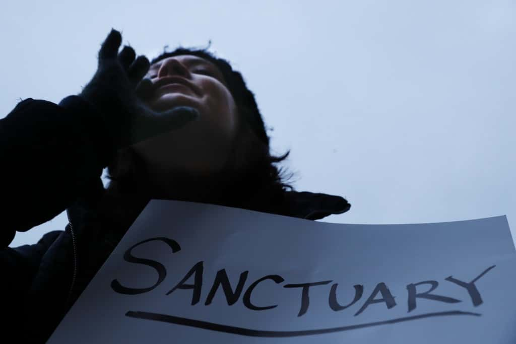 "Demonstrators chant against President Donald Trump's executive order temporarily banning immigrants from seven Muslim-majority countries from entering the U.S. and suspending the nation's refugee program Monday, Jan. 30, 2017, outside City Hall in Cincinnati. In addition, earlier in the day Mayor John Cranley declared Cincinnati a ""sanctuary city,"" meaning city will not enforce federal immigration laws against people who are here illegally, in keeping with current policy. (AP Photo/John Minchillo)"