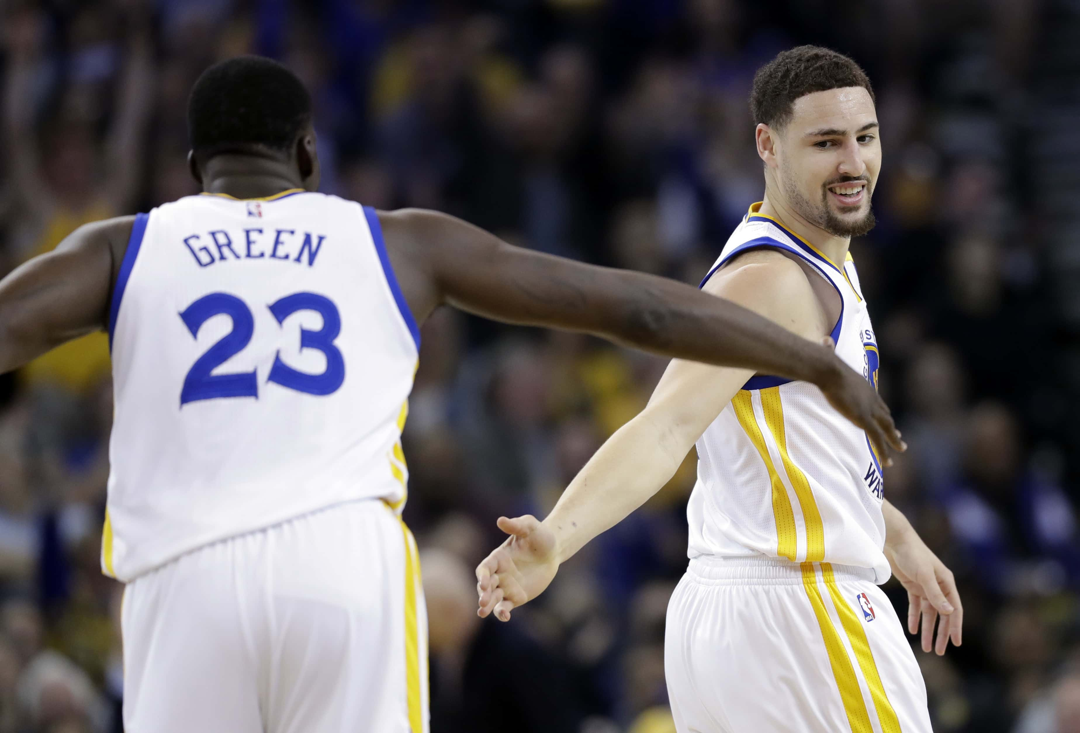 Golden State Warriors' Klay Thompson, right, shakes hands with teammate Draymond Green (23) after Thompson scored during the first half of an NBA basketball game against the Charlotte Hornets on Wednesday, Feb. 1, 2017, in Oakland, Calif. (AP Photo/Marcio Jose Sanchez)