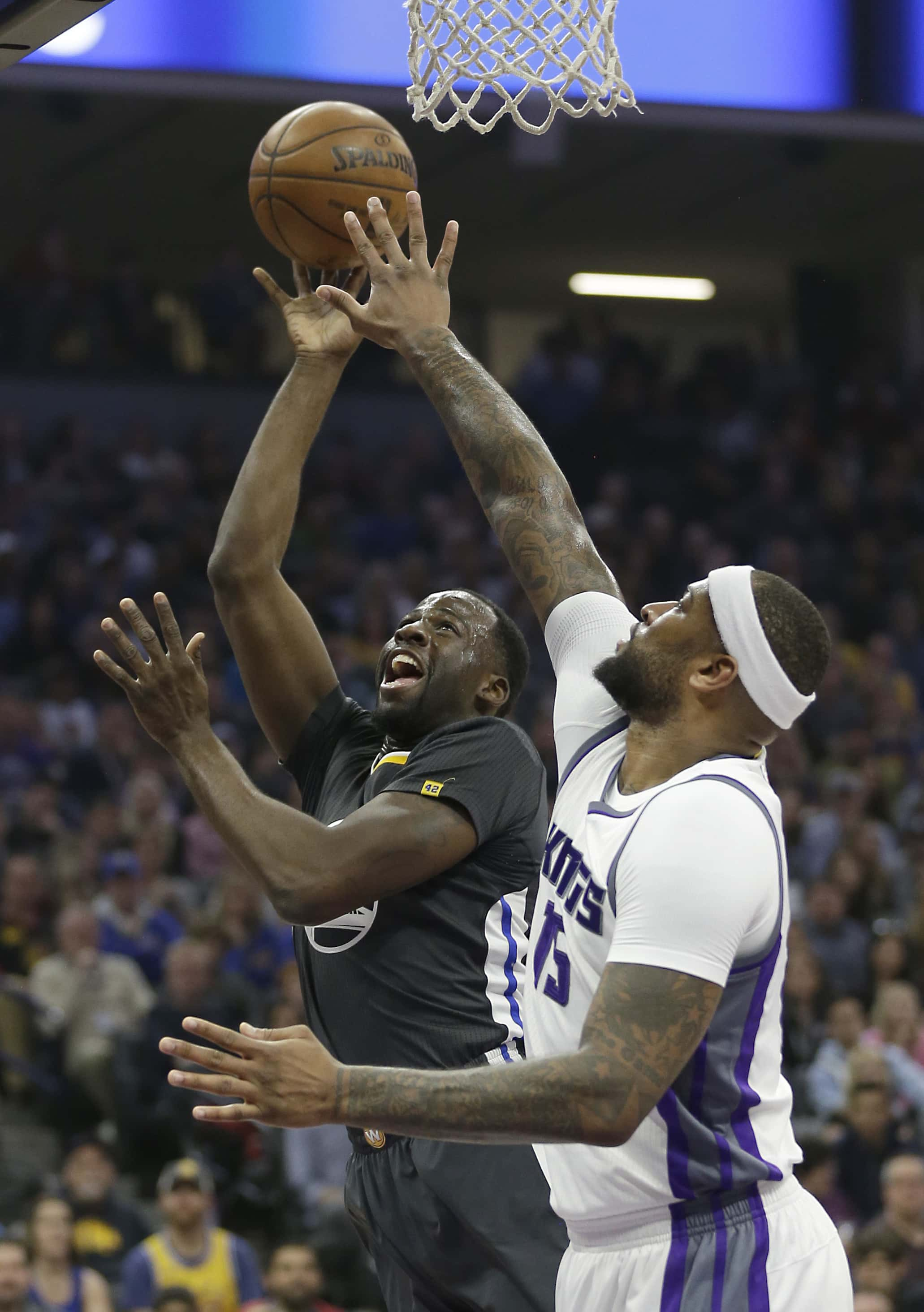 Golden State Warriors forward Draymond Green, left, goes to the basket against Sacramento Kings forward DeMarcus Cousins during the first half of an NBA basketball game Saturday, Feb. 4, 2017, in Sacramento, Calif. (AP Photo/Rich Pedroncelli)