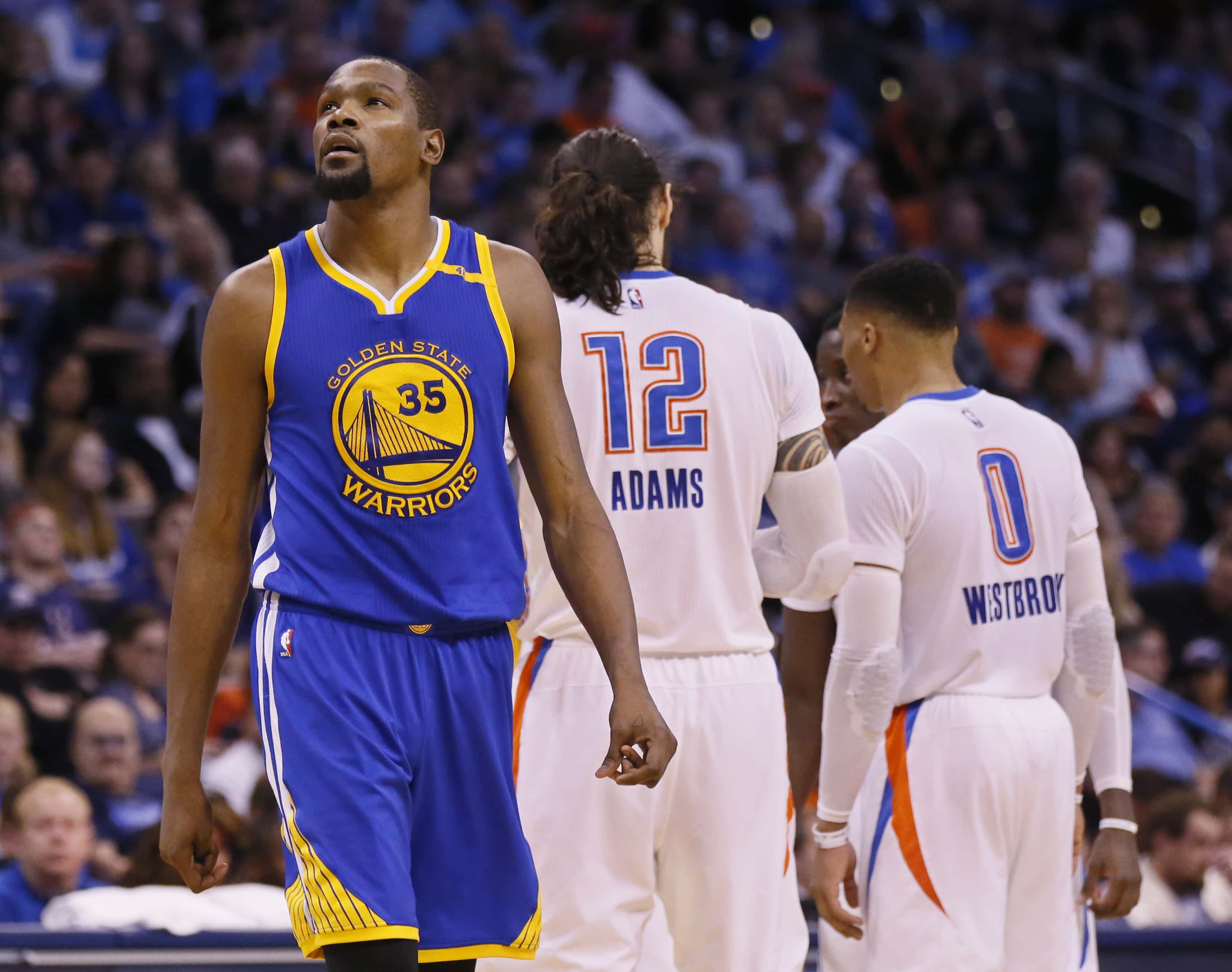 Golden State Warriors forward Kevin Durant (35) walks past former teammates Oklahoma City Thunder center Steven Adams (12) and guard Russell Westbrook (0) in the second quarter of an NBA basketball game in Oklahoma City, Saturday, Feb. 11, 2017. (AP Photo/Sue Ogrocki)