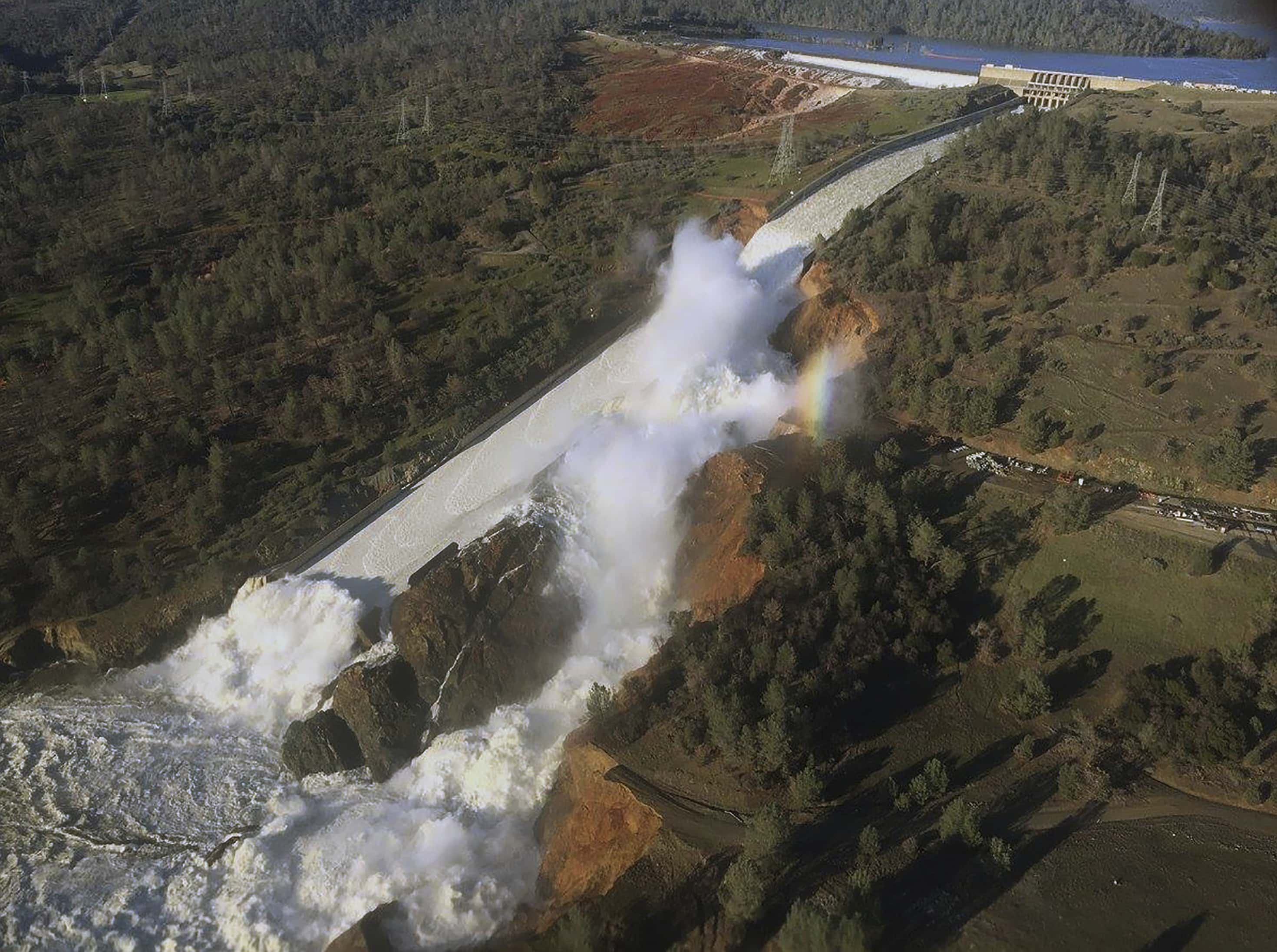 This Saturday, Feb. 11, 2017, aerial photo released by the California Department of Water Resources shows the damaged spillway with eroded hillside in Oroville, Calif. Water will continue to flow over an emergency spillway at the nation's tallest dam for another day or so, officials said Sunday. (William Croyle/California Department of Water Resources via AP)