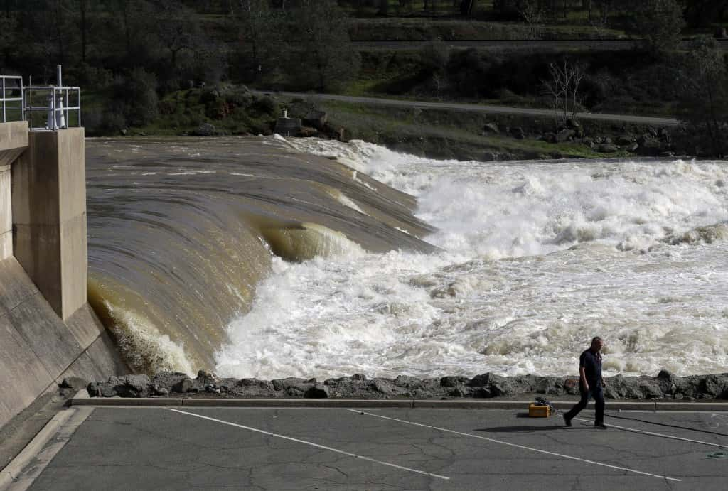 The Feather River flows with force through Oroville, Calif., downstream from a damaged dam Tuesday, Feb. 14, 2017. Workers are rushing to repair the barrier at the nation's tallest dam after authorities on Sunday ordered the evacuation for everyone living below the lake amid concerns the spillway could fail and send water roaring downstream. (AP Photo/Marcio Jose Sanchez)