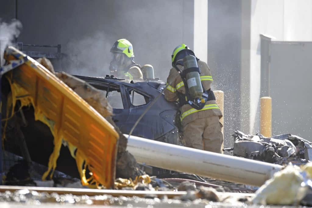 Emergency personnel work at a light plane crashed in Melbourne, Australia, Tuesday, Feb. 21, 2017. The plane crashed into a shopping mall, officials said. (Joe Castro/AAP Image via AP)
