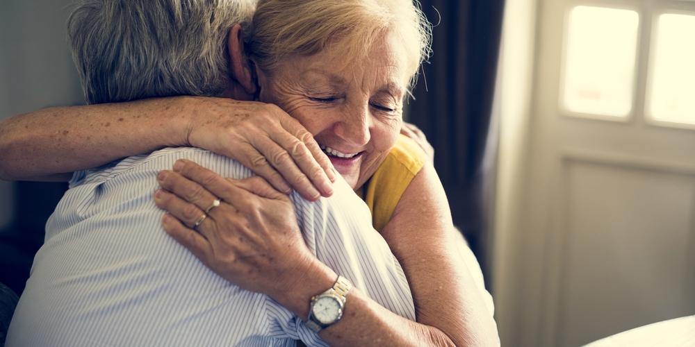 Two seniors hugging.