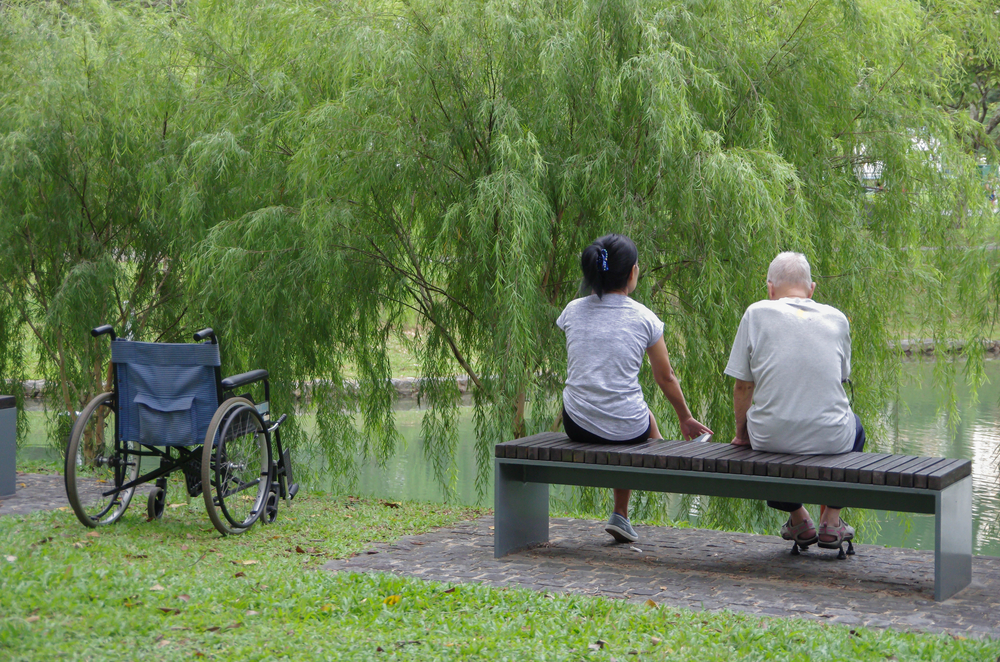 Senior and care giver sitting on a bench near a lake.