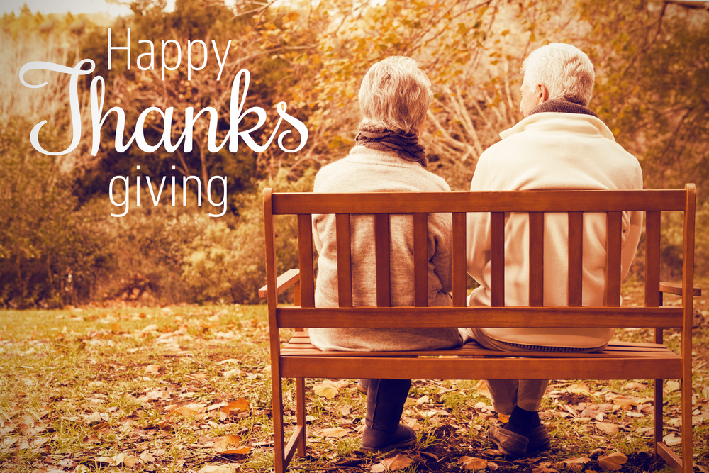 An elderly couple sitting on a bench with Happy Thanksgiving text next to them.