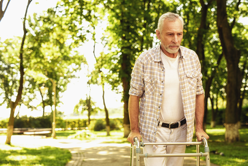 Elderly man using a walker going for a walk, as excersising can help someone sleep well at night.