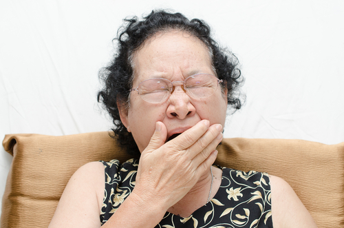 Elderly woman ywning, showing lack of sleeping well.