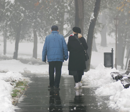 Two elderly people walking on the sidewalk during winter with snow on the ground.