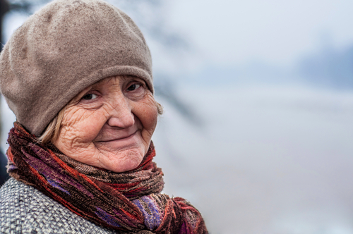 Elderly woman out in the cold during winter.