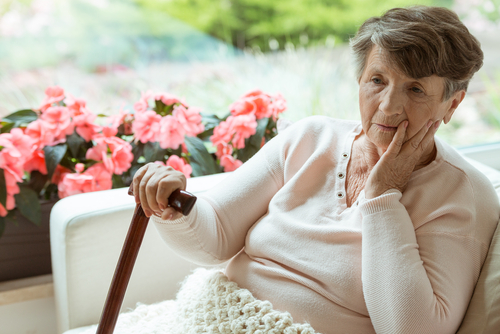 Elderly woman sitting in thought with a blanket on during early winter.