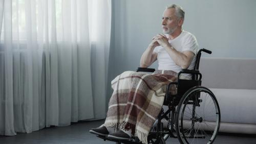 Elderly man in a wheelchair sitting inside in the dark, which can exacerbate Seasonal Affective Disorder.