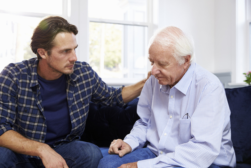 Elderly man experiencing Sundowner's Syndrome while his son comforts him.