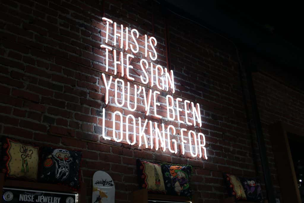 "Neon sign on a brick wall: ""This is the sign you've been looking for."""