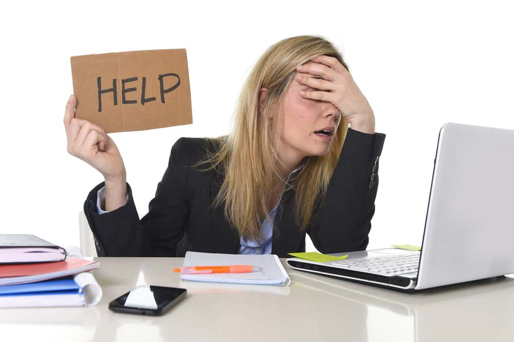 Stressed woman on laptop holding help sign