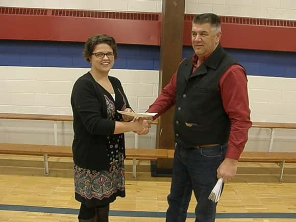 Far right DPC board president Greg Svenningsen hands a $5,000 check to Cathy Herbold of the Great Plains Food Bank.