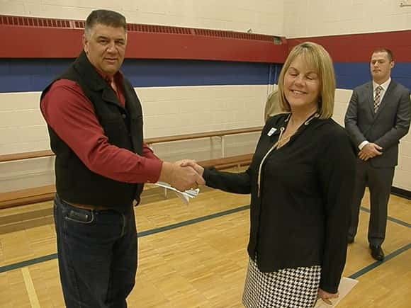 DPC board president Greg Svenningsen hands a $5,000 check to Lynn Speral of the American Red Cross.