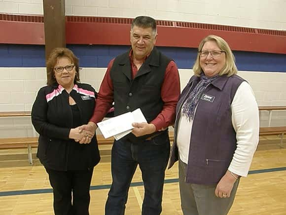 DPC board president Greg Svenningsen hands a $1,000 check to Beth Dewald and Pam Foertsch of the Freedom Resource Center and the Jamestown Business Center. Photos by Steve Urness.