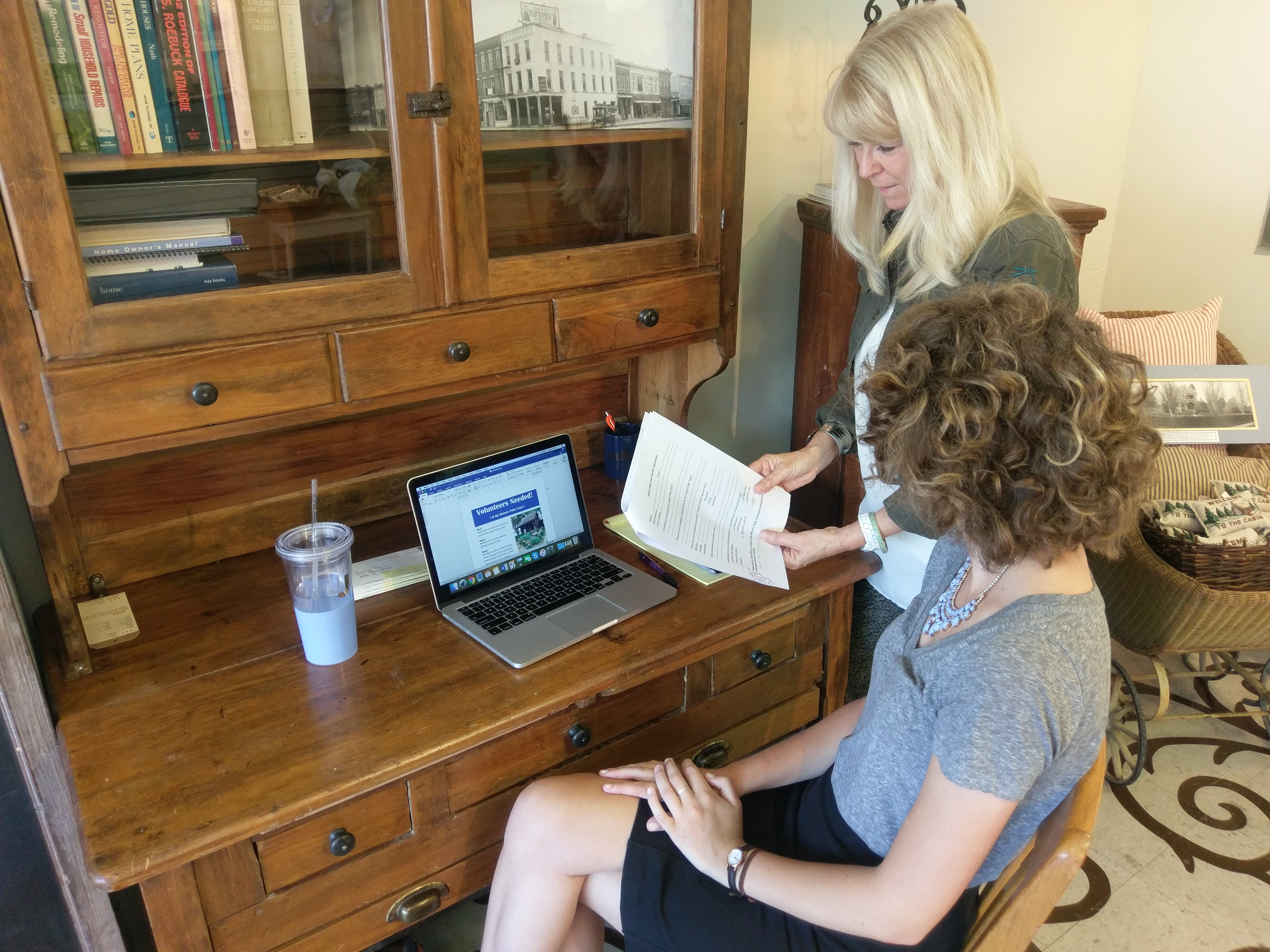 Lynn Branderhorst with Historic Pella Trust works with Intern Jesse Vos